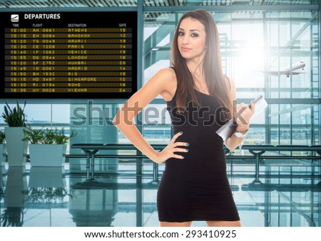 happy young woman using tablet computer at airport terminal - stock photo
