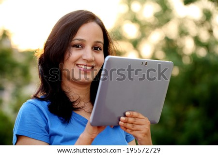 Happy young woman using tablet computer at outdoor - stock photo