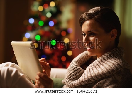 Happy young woman using tablet pc in front of christmas tree - stock photo