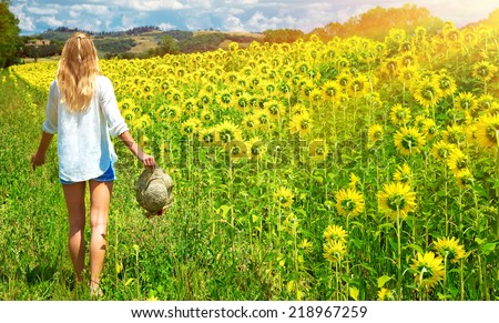 Happy young woman walking in fresh sunflowers field, agricultural landscape, autumnal nature, harvest season concept - stock photo
