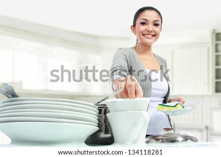 Happy Young Woman Washing Dishes in the kitchen - stock photo