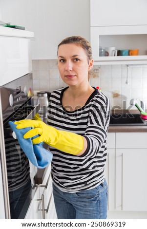 Happy young woman washing furniture in kitchen at home - stock photo