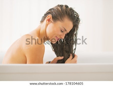 Happy young woman washing hair in bathtub - stock photo