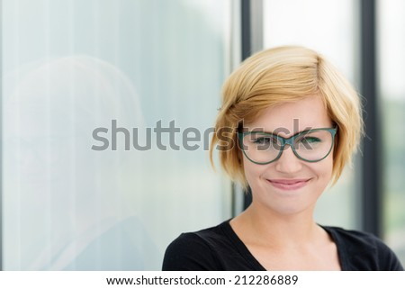 Happy young woman wearing glasses with a beaming smile, with copyspace to the side - stock photo
