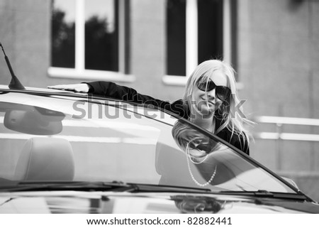 Happy young woman with a car - stock photo