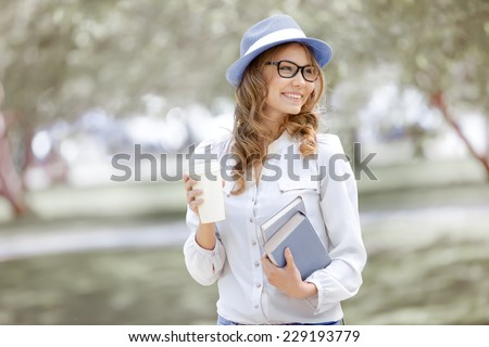 Happy young woman with a coffee-to-go, walking in a summer park and holding books for reading. - stock photo
