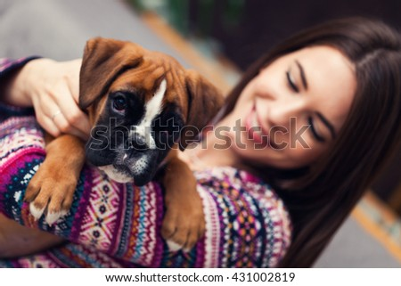 Happy young woman  with a cute german boxer puppy