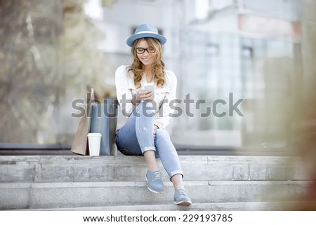 Happy young woman with a disposable coffee cup and shopping bags sitting on the stairs and using her smartphone for communication via wi-fi internet in a summer park. - stock photo
