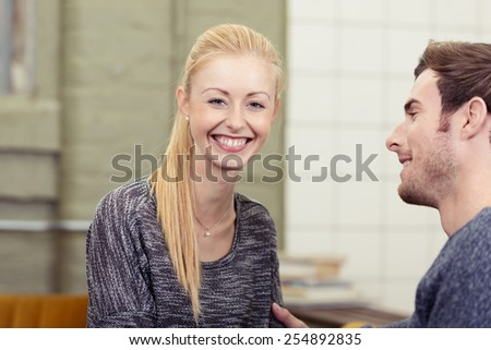 Happy young woman with a gorgeous beaming smile sitting at home with her husband looking at the camera, close up head and shoulders with the man in profile - stock photo