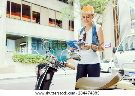 Happy young woman with a map and scooter - stock photo