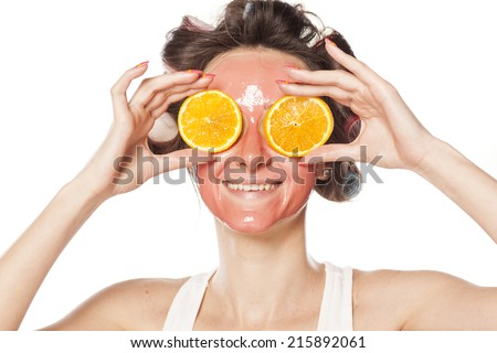 happy young woman with a mask and curlers holding a piece of orange on the eyes
