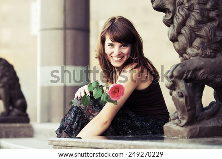 Happy young woman with a red rose sitting on the steps - stock photo