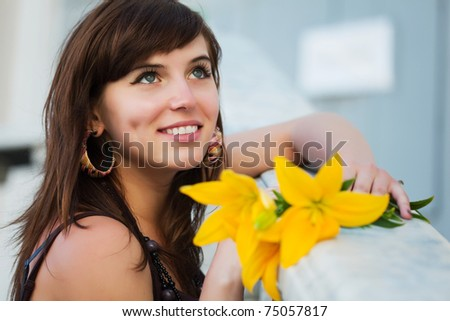 Happy young woman with a yellow lilies - stock photo
