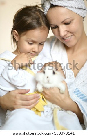 happy young woman with a young daughter and a rabbit