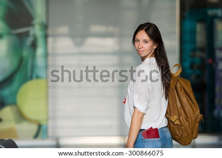 Happy young woman with air ticket and passports at airport waiting for boarding - stock photo