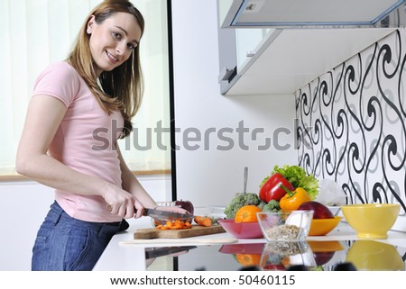 happy young  woman with apple in kitchen and other food and vegetables - stock photo