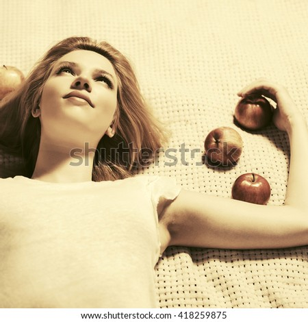 Happy young woman with apples lying on the cover. Female fashion model outdoor - stock photo