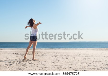 Happy young woman with arms outstretched at beach on a bright morning. Beautiful young woman with arms stretched out standing on a beach. Happy young woman feelling good and relaxing at the beach.  - stock photo