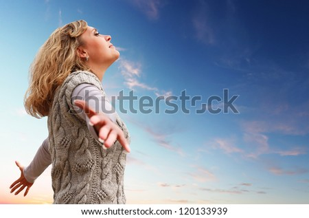 Happy young woman with arms raised towards a blue sky - stock photo