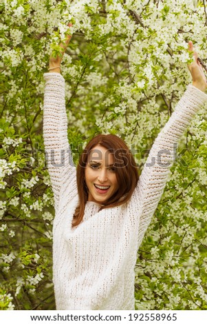 Happy young woman with arms raised up against blossoming spring trees  - stock photo
