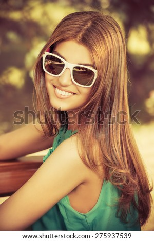 Happy young woman with beautiful smile outdoors. Summer day. - stock photo