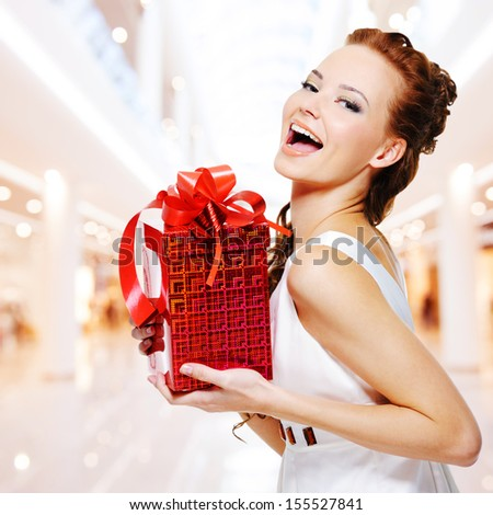 Happy young woman with birthday present in hands posing indoors - stock photo