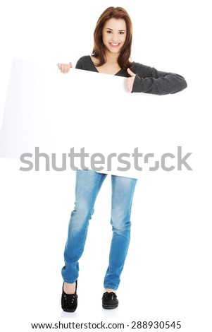 Happy young woman with blank billboard showing thumbs up - stock photo