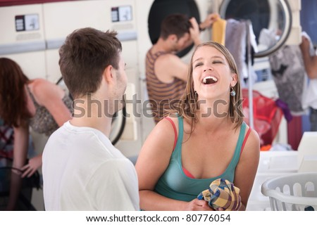 Happy young woman with boyfriend laughs out loud in the laundromat - stock photo