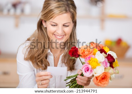 Happy young woman with bunch of flowers and card at home - stock photo