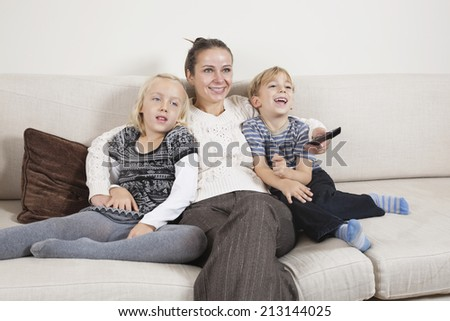Happy young woman with children on sofa watching TV - stock photo
