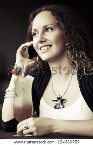 Happy young woman with cocktail calling on the phone