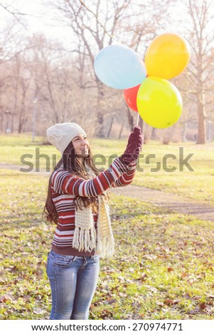Happy Young Woman With Colorful Balloons at beautiful sunny autumn day. Carefree Female lifestyle scene. - stock photo