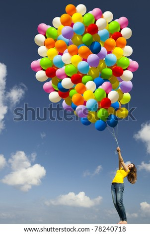 Happy young woman with colorful balloons on a green meadow - stock photo