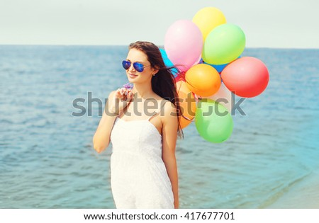 Happy young woman with colorful balloons on beach over sea enjoys summer day - stock photo