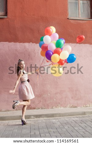 Happy young woman with colorful balloons walking on a street - outdoors - stock photo