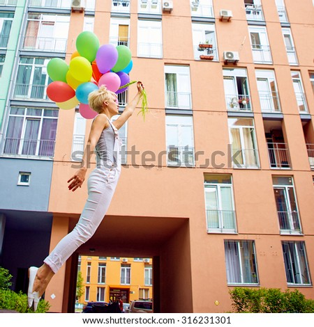 Happy young woman with colorful latex balloons, outdoor, jumping - stock photo