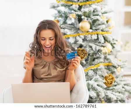 Happy young woman with credit card and laptop rejoicing - stock photo