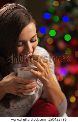 Happy young woman with cup of hot beverage eating marshmallow in front of christmas lights - stock photo