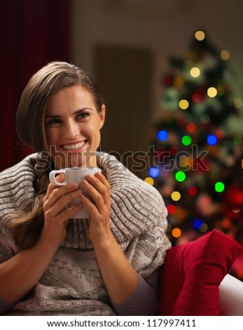 Happy young woman with cup of hot chocolate in front of Christmas lights - stock photo
