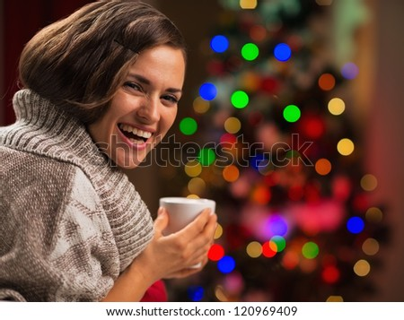 Happy young woman with cup of hot chocolate in front of Christmas tree - stock photo
