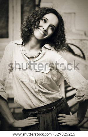Happy young woman with curly hairs. Stylish fashion model outdoor