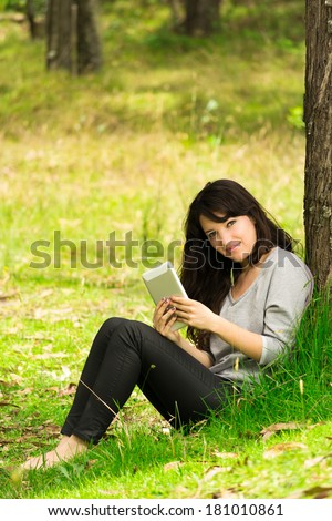 Happy young woman with digital tablet sitting on grass in park - stock photo
