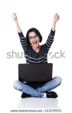 Happy young woman with fists up using her laptop, isolated on white. - stock photo