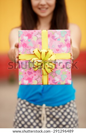 Happy young woman with gift box, smiling girl with birthday gifts outdoor, beautiful female at birthday party with present, joyful lady hold gifts outdoor portrait, instagram style color filter  - stock photo