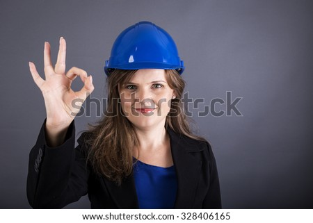 Happy young woman  with hardhat  showing ok sign over gray background - stock photo