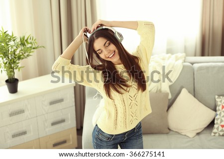 Happy young woman with headphones dancing and listening to music at home - stock photo