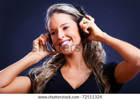 Happy young woman with headphones. Over dark   background