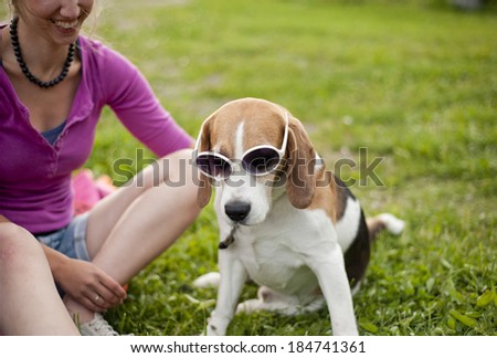 Happy young woman with her beagle dog in the green park