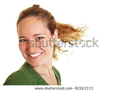 Happy young woman with her brunette hair flying in the wind - stock photo