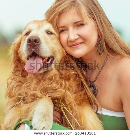 happy young woman with her dog golden retriever in rural areas in summer close-up - stock photo